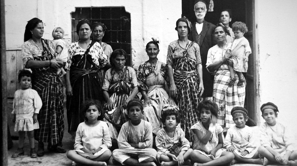 Svartvitt foto på barn och vuxna framför ett hus