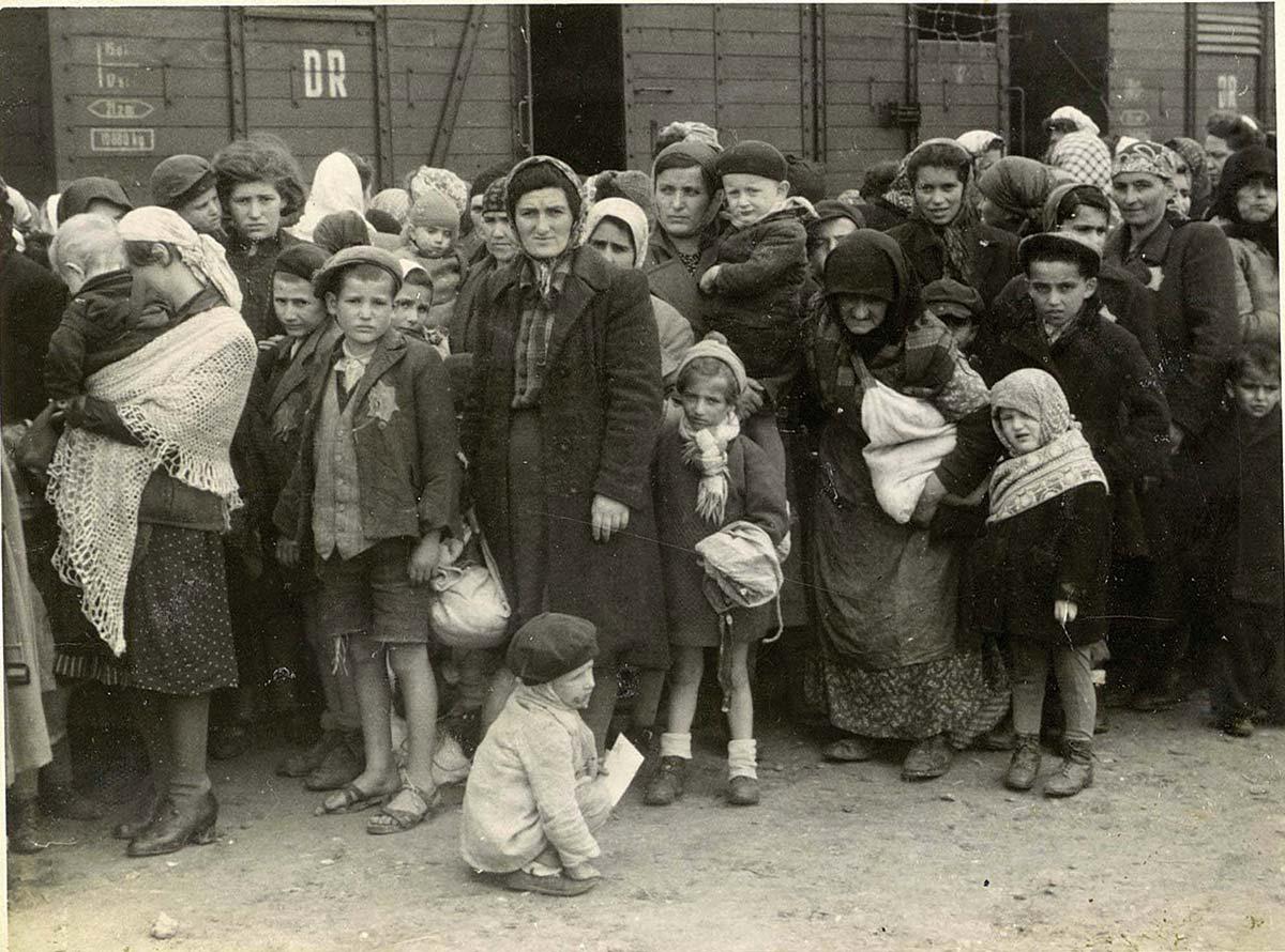 Foto på judiska kvinnor och barn framför en tågvagn