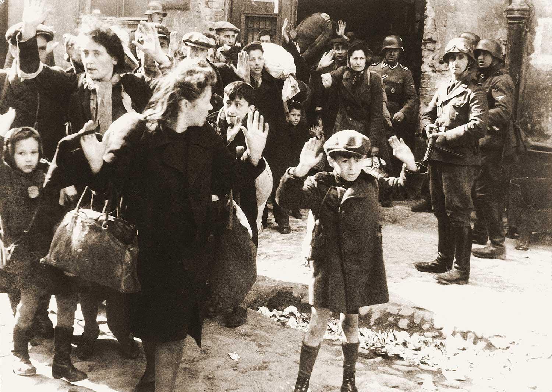 Judiska barn och kvinnor med resta händer eftersom nazister siktar på dem med vapen