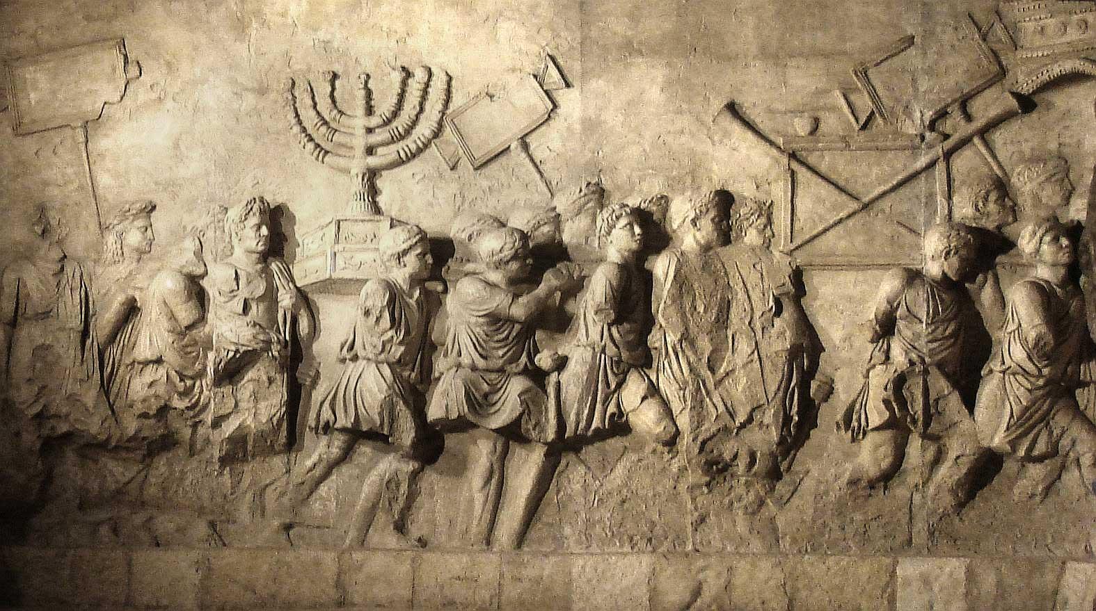Foto på Titusbågen i Rom med avbildning av romare som bär byte från judarnas tempel.